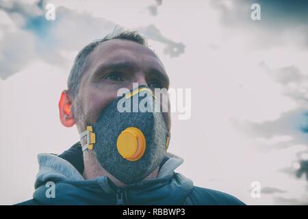Hombre que llevaba un verdadero anti-contaminación, anti-virus de smog y máscara facial; una densa niebla en el aire