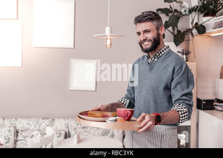 Feliz alegre hombre llevar comida a la mesa