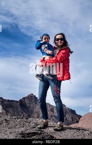 Una bonita foto de una bella mujer y su hijo de pie sobre una montaña en el fondo de un cielo nublado
