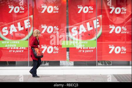 Mujer paseando venta firmar en apariencia nueva ventana almacén en Stockton High street. Stockton on Tees, al noreste de Inglaterra. UK Foto de stock
