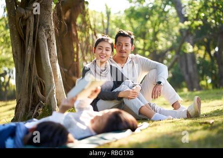 Dos niños asiáticos chico y chica divirtiéndose tumbado sobre el césped a leer un libro con sus padres sentados mirando en el fondo. Foto de stock