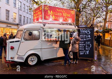 Las personas que se sirven bebidas calientes en vides mulled wine bar (retro camioneta móvil servicio de catering) en la fiesta de Navidad al aire libre mercado - York, Inglaterra, Reino Unido.