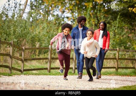 Los niños de raza mixta corriendo delante de sus padres en un trazado durante el paseo en familia en el campo, bajo el ángulo