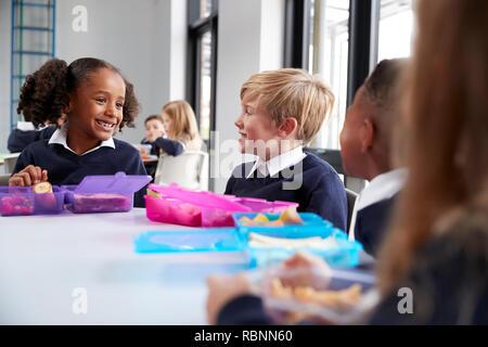 La escuela primaria los niños sentados a la mesa comiendo sus comidas empaquetadas y conversar, cerrar