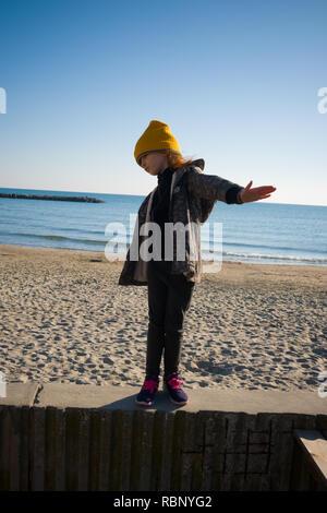 Una niña de seis años con yellow woolly hat y rompevientos destaca sobre un rompeolas mientras pretendiendo volar. Día de otoño en Palavas les Flots, Francia