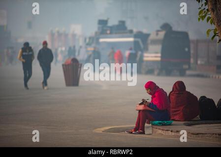Mañana temprana escena delante de la Fortaleza Roja de Delhi con una mujer sentada y escribiendo en su cuaderno y peatones en el fondo.