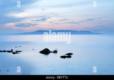 Piso tranquilo mar,viento día,península de Howth,suburbio del condado de Dublín como visto a través de la bahía de Dublín, Irlanda.