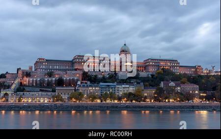 Castillo de Buda, con vistas al río Danubio, en Budapest. Es temprano en la noche, y el castillo está iluminado con luces, reflexionando sobre el río