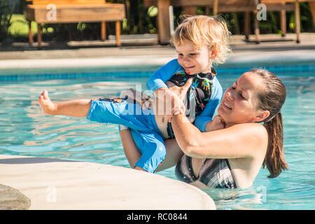 Un muchacho feliz y su madre salir de la piscina