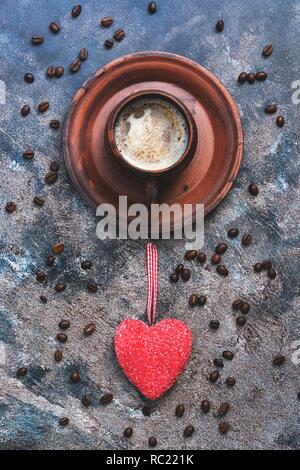 Café caliente y el corazón rojo sobre un fondo abstracto rústico. El concepto de celebración, el día de los enamorados. Vista desde arriba