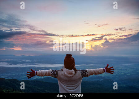 Mujer turista en un suéter vestido brazos extendidos, permanente feliz mientras contempla el bonito paisaje natural de la selva y la montaña durante el
