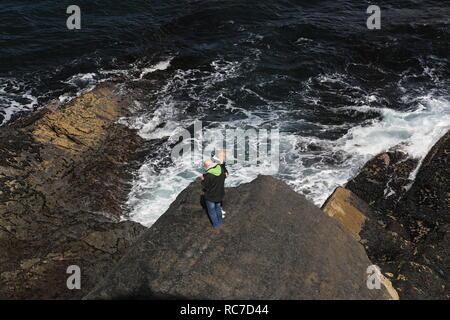 Dos personas de pie en el borde del acantilado con vistas del atlántico salvaje, condado de Kerry, Irlanda,