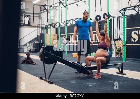 Formador guiar a la mujer embarazada con pesas en el gimnasio