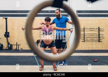 Formador guiar a la mujer embarazada con cuerdas en el gimnasio
