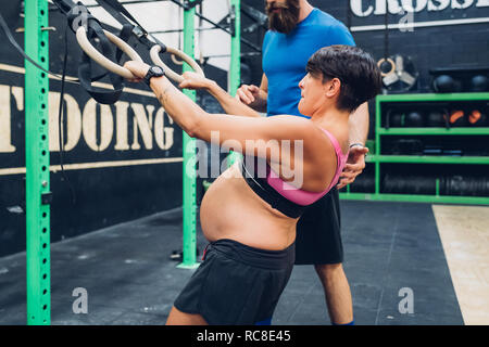 Formador guiando embarazada utilizando equipo de ejercicio en el gimnasio