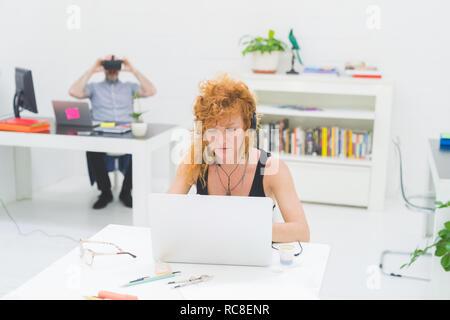 La empresaria escribiendo en el portátil en la oficina mientras escucha los auriculares