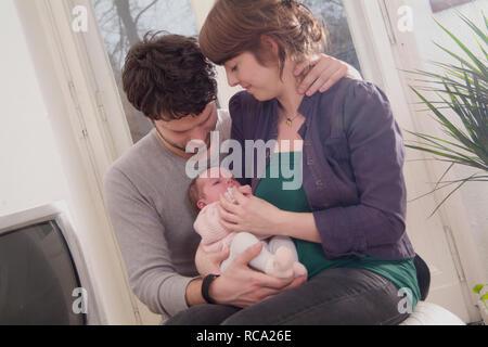 Junge Eltern halten ihre Tochter neugeborene im, brazo tipo das ist 12 Tage alt   padres jóvenes sostiene a su bebé recién nacido en sus brazos - el bebé ist 12