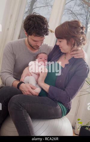Junge Eltern halten ihre Tochter neugeborene im, brazo tipo das ist 12 Tage alt | padres jóvenes sostiene a su bebé recién nacido en sus brazos - el bebé ist 12