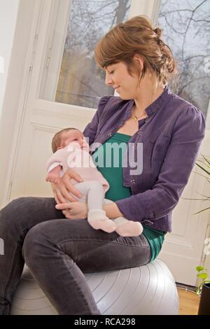 Junge Mutter ihre Tochter hält neugeborene im, brazo tipo das ist 12 Tage alt   joven madre sostiene a su bebé recién nacido en sus brazos - el bebé ist 12 días