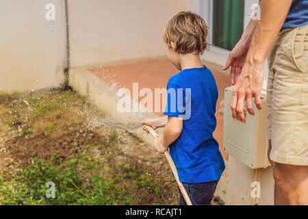 Cute little boy niño regar las plantas con regadera en el jardín. Adorable pequeño niño ayudando a los padres a cultivar hortalizas y divertirse. Actividades con los niños al aire libre
