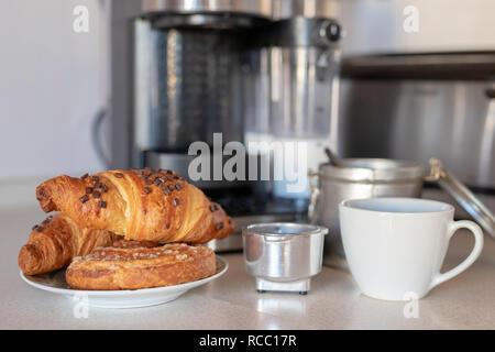 Café recién hecho de una máquina de café y un croissant Dulce sabroso. Desayuno en la cocina de hogar. Luz de fondo.