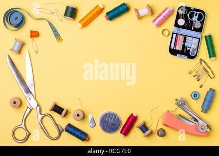 Composición con hilos de coser y accesorios: tijeras, centímetro, pasadores sobre fondo amarillo.