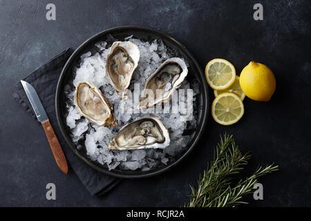 Ostras frescas en un plato con hielo sobre fondo negro