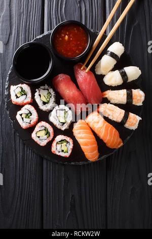 Sushis japonés Comida. Maki ys rollos con el atún, el salmón, camarones, cangrejo y aguacate con dos salsas de cerca en una placa de pizarra. Vista superior de la vertical de abo