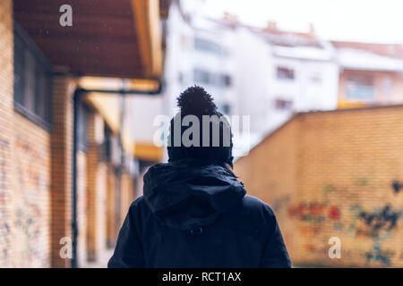 Vista trasera de una mujer adulta casual caminando por las calles de la ciudad urbana durante la luz nevadas en invierno