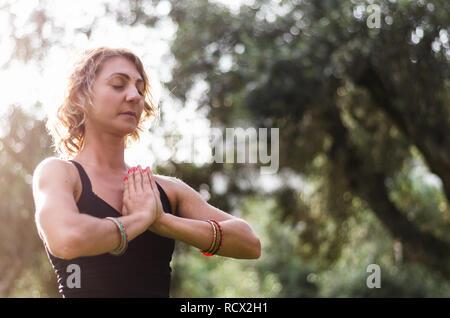 Hermosa joven medita en Padmasana asanas de yoga - Lotus plantear sobre la plataforma de madera en el parque de otoño.
