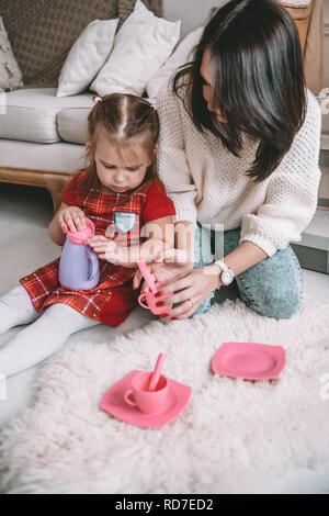 Feliz familia cariñosa. Madre e hija girl play té-parte y beben té en tazas en la sala de niños. Gracioso mamá y precioso niño divirtiéndose en interiores