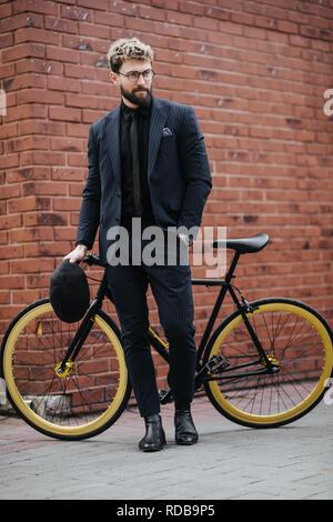 Empresario elegante de pie con su bicicleta contra la pared de ladrillo