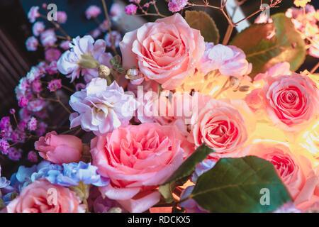 Peony rosas y flores pequeñas con un resplandor interior. Hermosas flores cerca de fondo Foto de stock