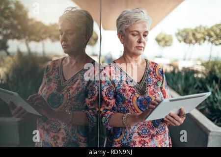 Retrato de una hermosa mujer de mediana edad de pelo gris trabajando en tableta digital