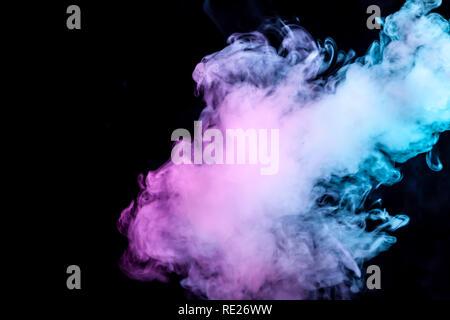 Nubes aisladas de humo de color: azul, rojo, verde, rosa; al desplazarse sobre un fondo negro en la oscuridad cerca.