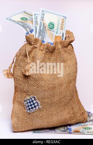 Cien dólares en una bolsa de arpillera sobre un fondo blanco.