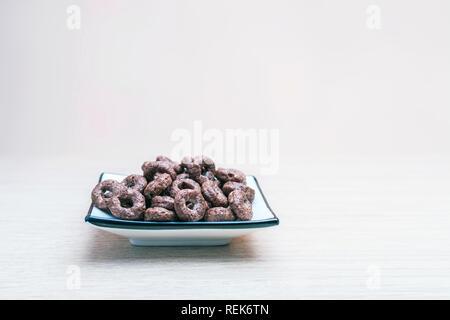 Grano entero de Chocolate Crujiente cereales de avena en una plaza redonda Dish on light mesa de madera. Orgánica saludable desayuno, comida, merienda concepto con Copy-Spac
