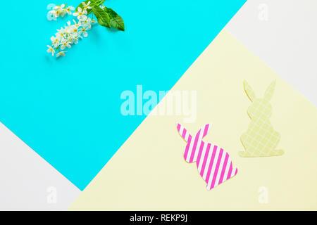 Conejito de Pascua de papel y las flores de la primavera. Mínimo concepto de pascua. Vista superior de la lay de fondo plano. Copie el espacio.