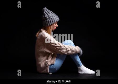 La niña está sentada sola en el suelo sobre un fondo negro de la vacuidad, abrazando sus piernas con sus manos y mirando hacia abajo, llorando en una esquina de una d
