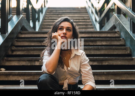 Retrato de mujer joven sentada en las escaleras
