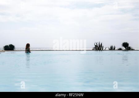 Joven pelirroja mujer nadar en una piscina de borde infinito en bikini cerca del océano mirar muy lejos Foto de stock