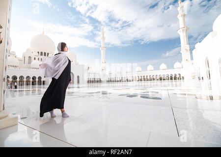 Árabe tradicionalmente vestidos mujer vistiendo burka negra wisiting Gran Mezquita de Sheikh Zayed, en Abu Dhabi, Emiratos Árabes Unidos.