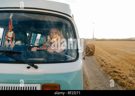 Feliz joven conduciendo autocaravana en paisaje rural