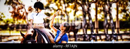 Vista lateral de la mujer dando a alta cinco a la chica sentada a caballo. Foto de stock