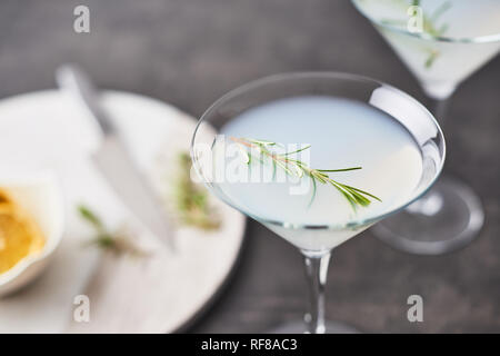 Copa de Verano. Bebidas de verano refrescante cóctel margarita con romero y cítricos o espumosos gin y limonada en tabla de hormigón oscuro. Cop