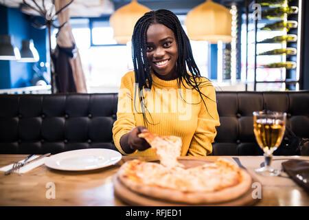 Joven muchacha africana en jersey amarillo comer pizza en el restaurante. Foto de stock