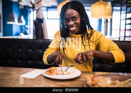 Los jóvenes afro americana mujer vistiendo en jersey amarillo comer pizza en el café