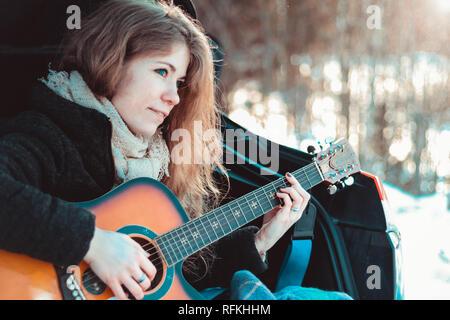 Chica tocando la guitarra sentado en el maletero del coche Foto de stock