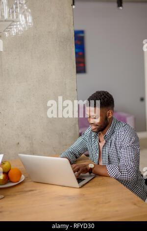 Hombre africano en ropa casual sentado a la mesa en frente de abrir el portátil en casa