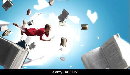 Relajado mujer levanta en el aire volando entre libros. Mixed Media Foto de stock